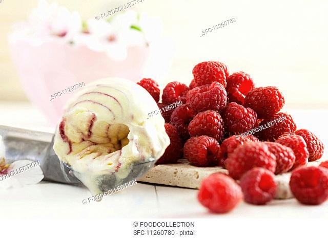 Vanilla and raspberry ice cream in an ice cream scoop next to a pile of fresh raspberries