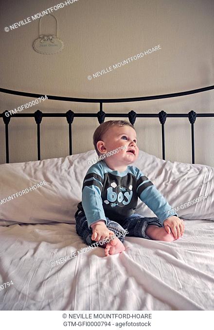 Baby boy sitting on bed