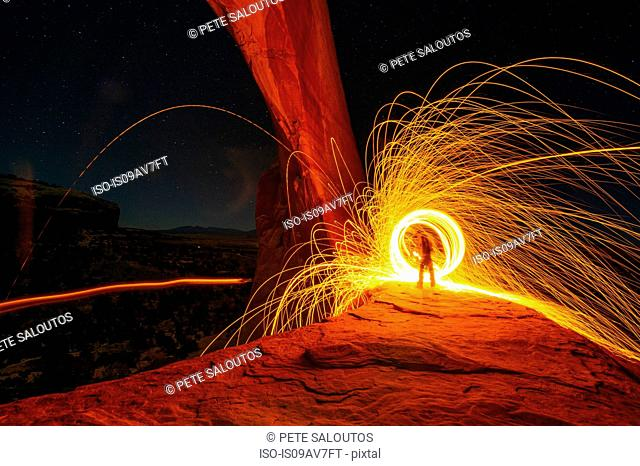 Silhouetted person creating yellow circular light trails on arch rock formation at night, Utah, USA