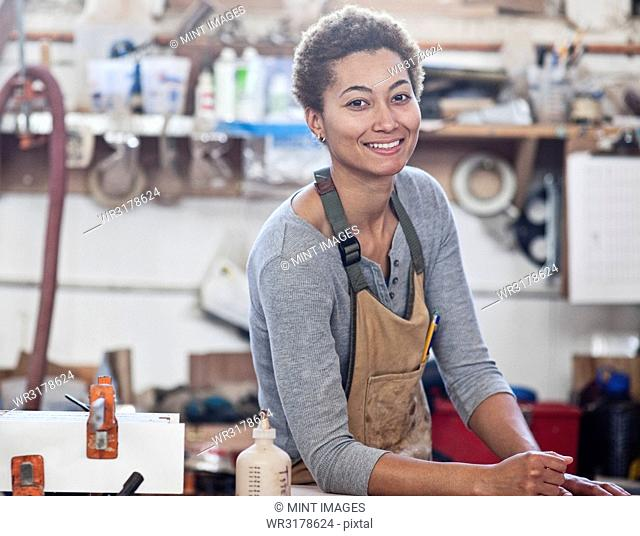 View of a smiling black woman factory worker at her work station in a woodworking factory