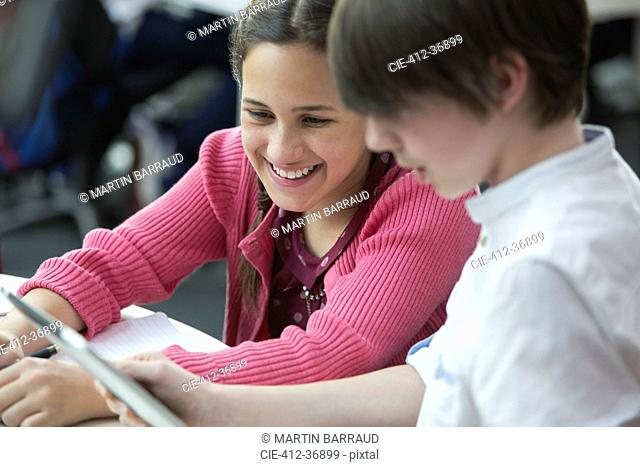 Smiling students using digital tablet in classroom