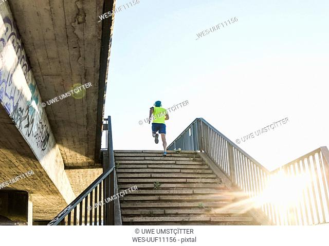 Young athlete jogging up stairs in the city