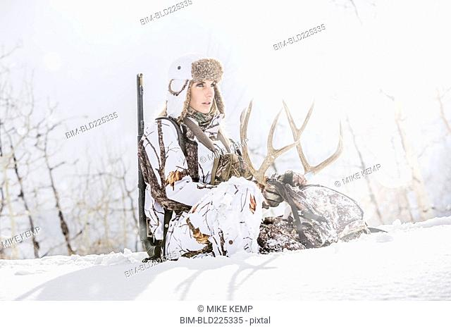Caucasian woman hunting in forest holding antlers