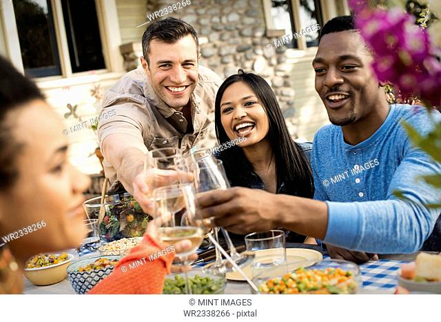 Friends around a table, men and women laughing and clinking wine glasses in a toast