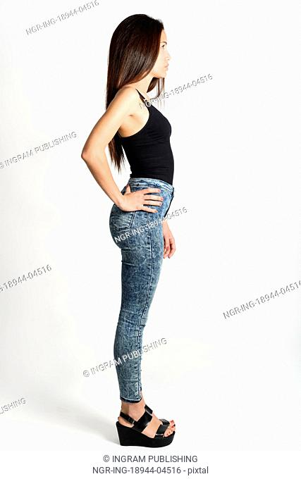 Young woman wearing black tank top and blue jeans on white background. Studio shot