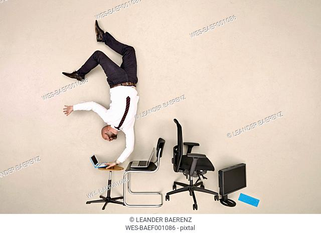 Businessman doing handstand while working on laptop