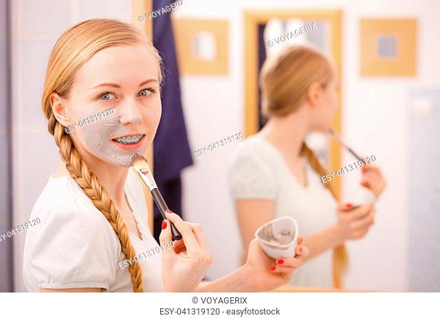 Skincare. Blonde woman in bathroom looking at mirror, being apply with brush gray clay mud mask to her face. Young lady taking care of skin