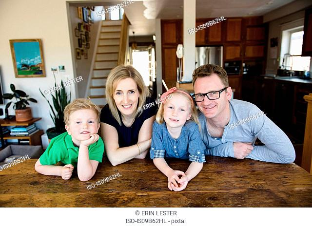 Portrait of parents at kitchen table with daughter and son