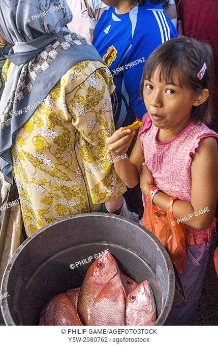 Young Malay girl with her parents at the Geylang Market, Singapore