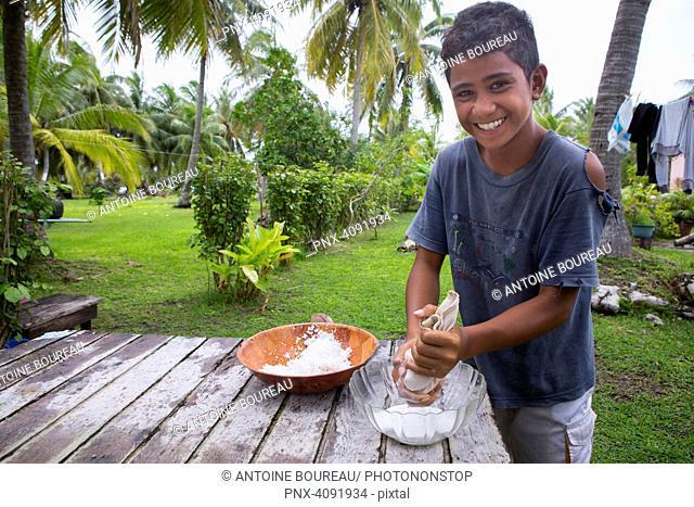 Terevau, 11, presses copra in a cloth to extract coconut milk, Motu Tiapaa, Maupiti Island, Leeward Islands, French Polynesia