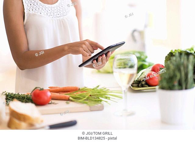 Hispanic woman cooking with digital tablet in kitchen