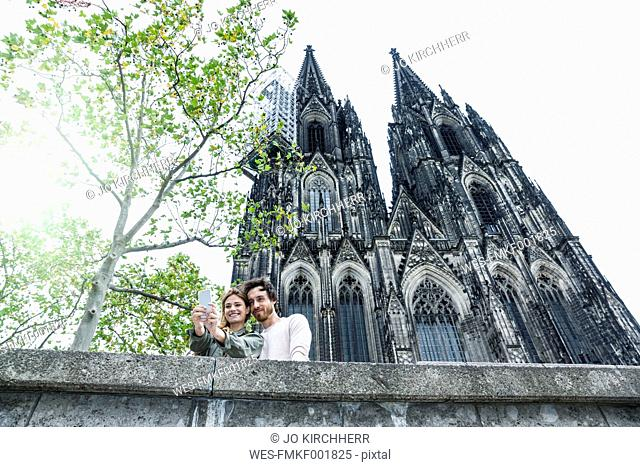 Germany, Cologne, portrait of young couple taking a selfie in front of Cologne Cathedral