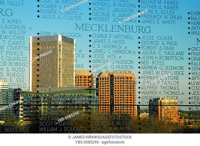 Names of Virginia soldiers killed in World War II are etched in glass, with the city of Richmond Virginia behind it