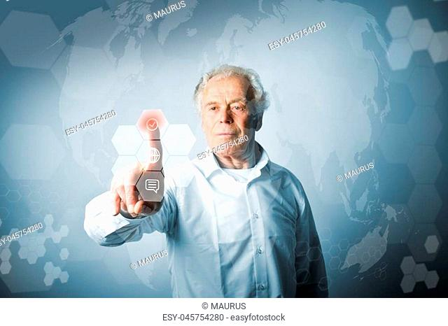 Old man in white is pushing the virtual hexagonal button. Innovative technology concept