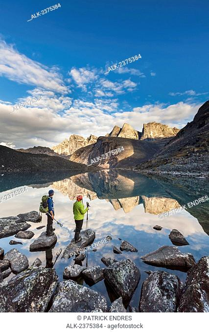 Hikers view East and West Maiden and Camel peaks as they reflect in a mountain lake in the Arrigetch Peaks, Gates of the Arctic National Park, Alaska