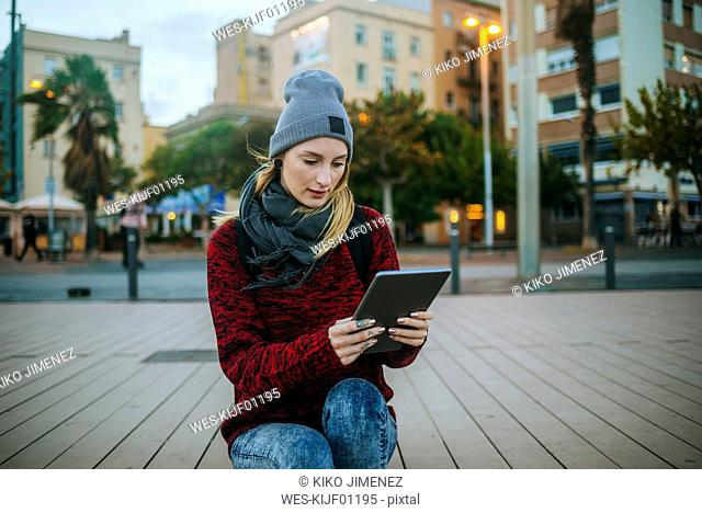 Spain, Barcelona, young woman using a tablet outside in winter