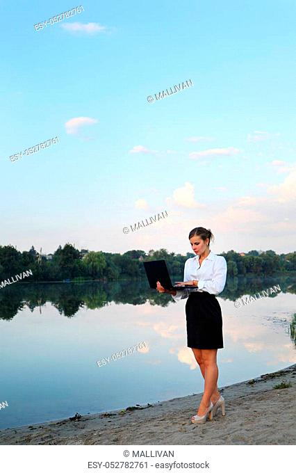 Concept illustrating remote work, business woman with laptop on the beach