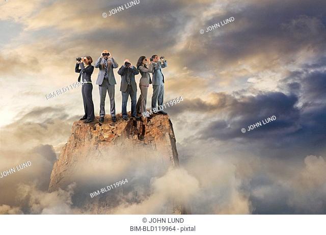 Business people with binoculars on mountaintop