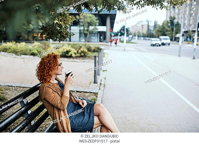 Young woman sitting on a bench, drinking coffee