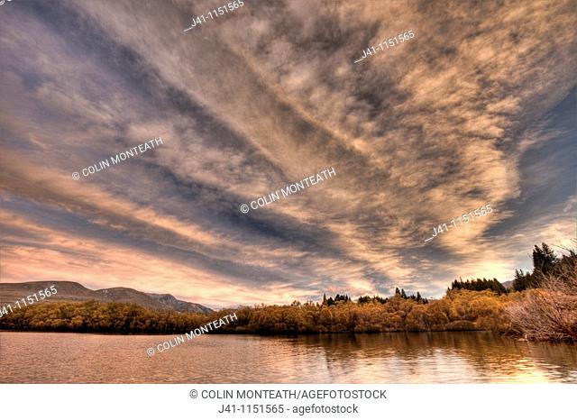 Frontal weather system from SW moves high over Lake Heron sheep & cattle station at dawn, autumn, Canterbury