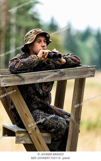 Teenager with binoculars on hunting tower