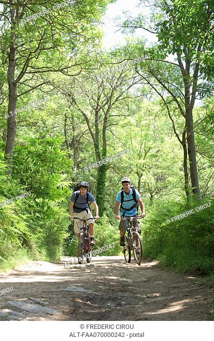 Men riding bicycles in woods