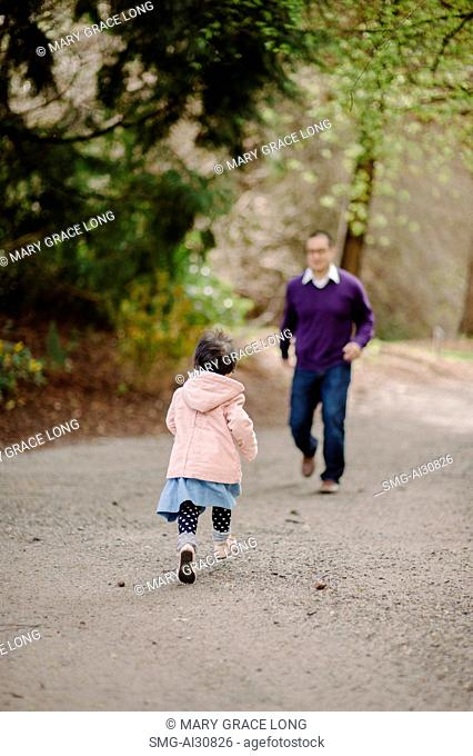USA, Daughter (2-3) running towards father in park