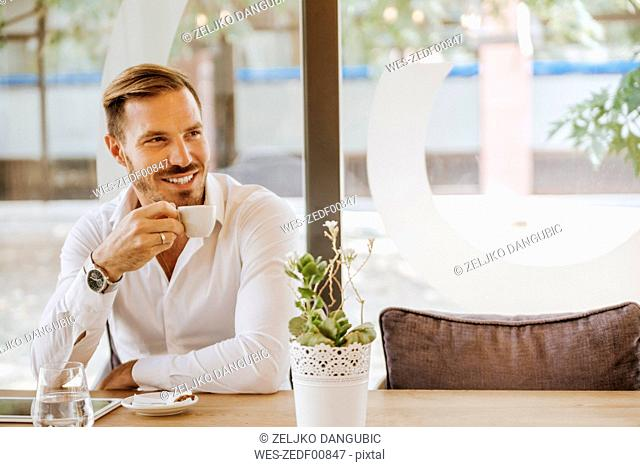 Smiling man with tablet drinking espresso in a cafe