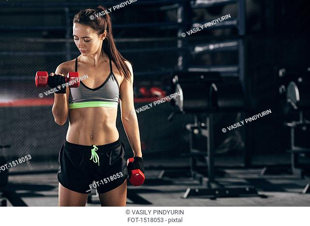 Female athlete lifting with dumbbells at gym
