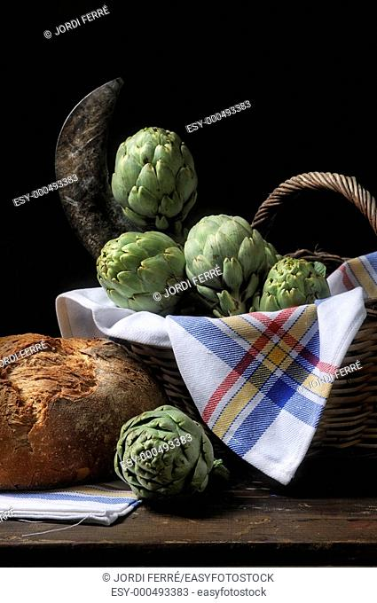 Basket with artichokes and a loaf of bread, dark background, Bodegón de cesto con alcachofas y hogaza de pan, fondo oscuro