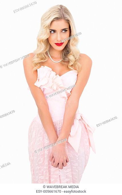 Concentrated blonde model in pink dress posing holding her hands and looking away