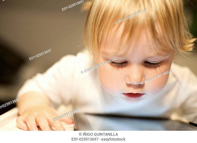 blonde nineteen month age baby white sweater looking at close digital tablet inside home