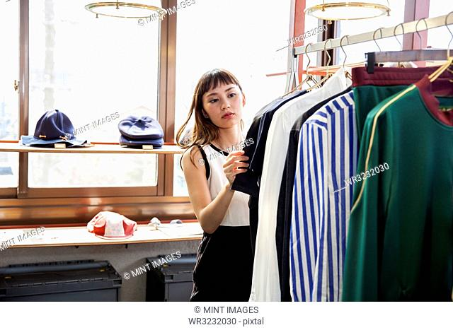 Japanese saleswoman standing in clothing store, looking at shirt