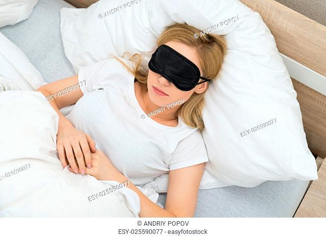 Young Woman Sleeping With Sleep Mask In Bedroom