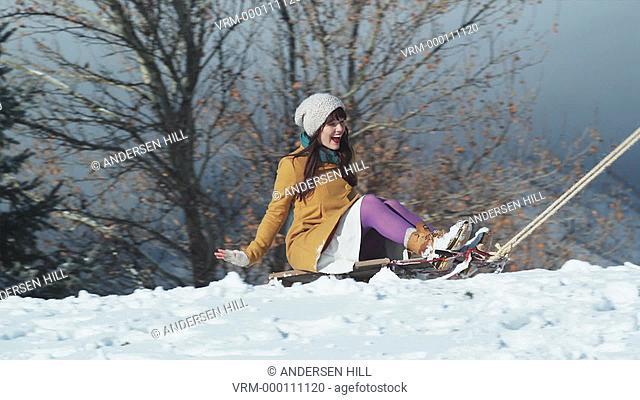 boyfriend pulling his girlfriend through the snow on a sled