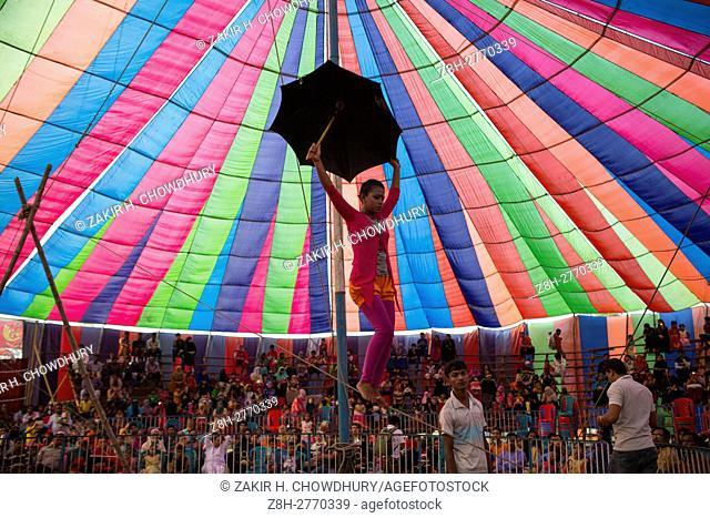 DHAKA, BANGLADESH - NOVEMBER 29 : Acrobate doing trapeze inside a circus tent beside in Dhaka, Banhladesh on November 29, 2016.