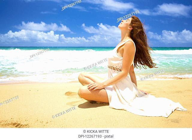 A woman sitting on the sand at the water's edge soaking up the sun; Kealia, Kauai, Hawaii, United States of America