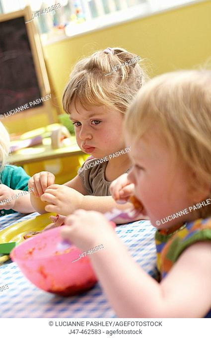 Children sitting eating lunch at nursery