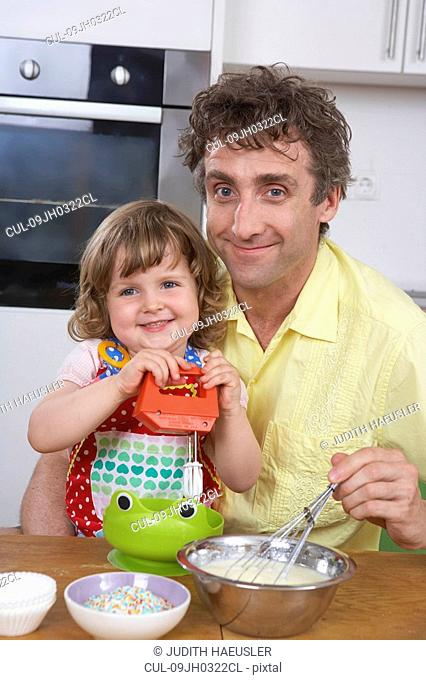 Father and daughter, stirring batter