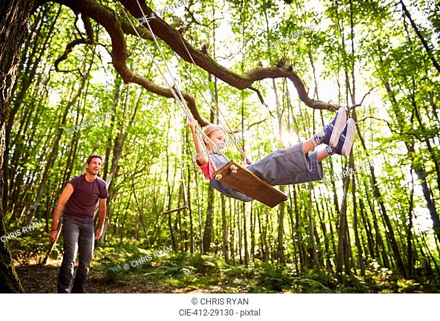 Father pushing daughter on rope swing in forest
