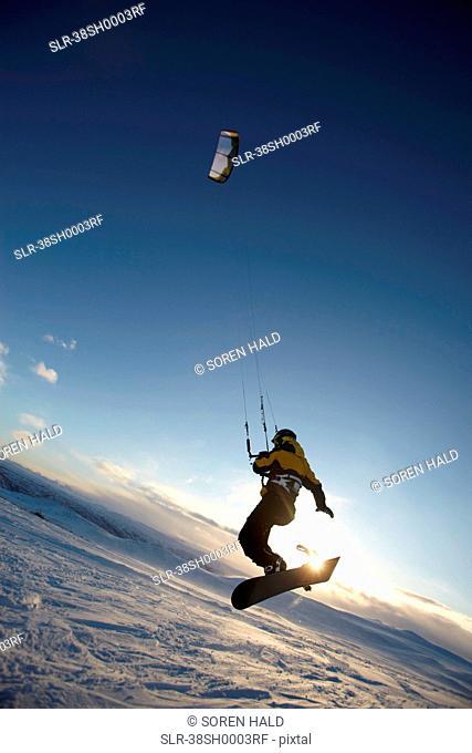 Man windsurfing on snowboard