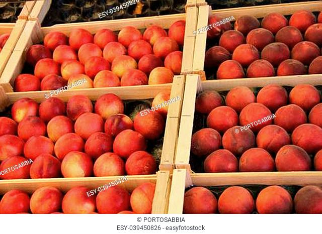 Big peaches displayed in wooden crates at a French market