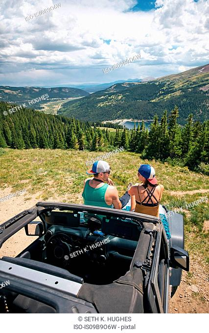 Rear view of road trip couple sitting on four wheel convertible hood in Rocky mountains, Breckenridge, Colorado, USA