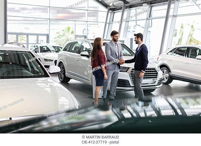 Car salesman and customers handshaking in car dealership showroom