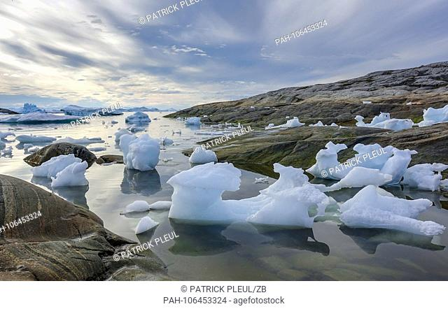 19.06.2018, Gronland, Denmark: Broken ice from icebergs drifts in the water off the coastal town of Ilulissat in western Greenland