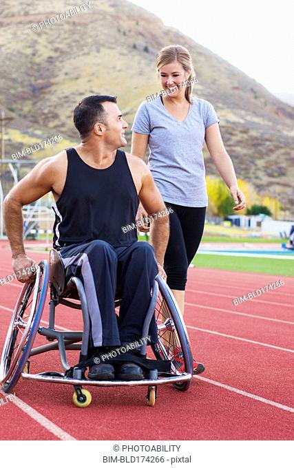 Paraplegic athlete in wheelchair with girlfriend on track