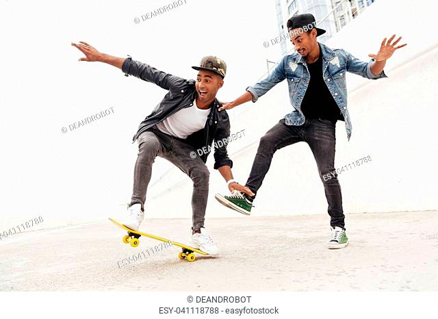 Picture of emotional two young african men friends walking outdoors with skateboard