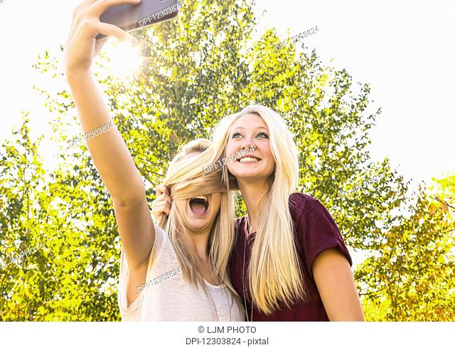 Two sisters having fun outdoors in a city park in autumn and taking selfies of themselves when one sister covered the other sister's face with her hair;...