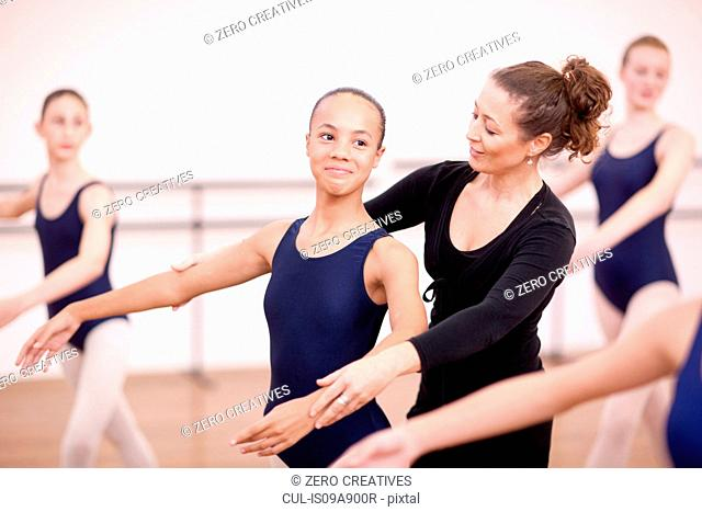 Teacher adjusting arms of shy teenage ballerina