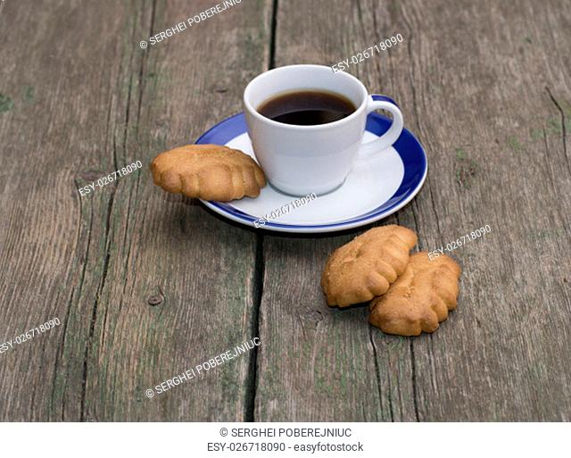 cup of coffee and some cookies on a wooden table, a subject drinks